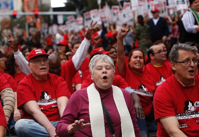 The Rev. Kathryn A. Obenour, middle, participates in a protest as members of the Culinary Union block traffic on the Las Vegas Strip in front of the Cosmopolitan Hotel on Wednesday.