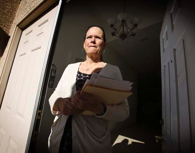 Cathy Thran holds loan forms Monday outside her northwest Las Vegas home. Thran sought a principal reduction through the U.S. Treasury's Hardest-Hit Fund. She completed financial counseling  ...