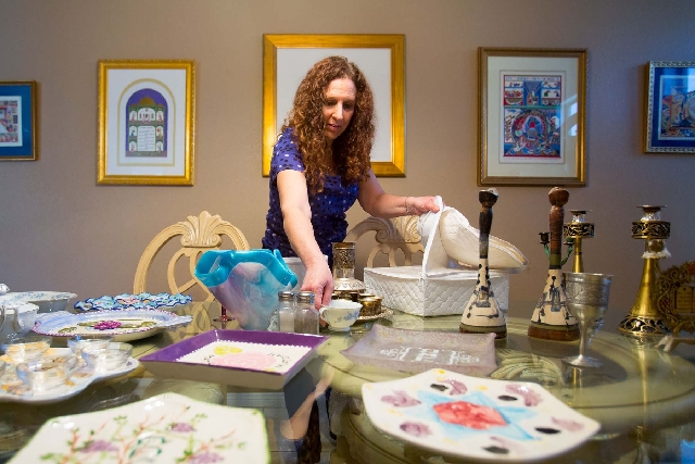 Lori Chenin-Frankl displays some of her family's Passover Seder plates at her Henderson home.