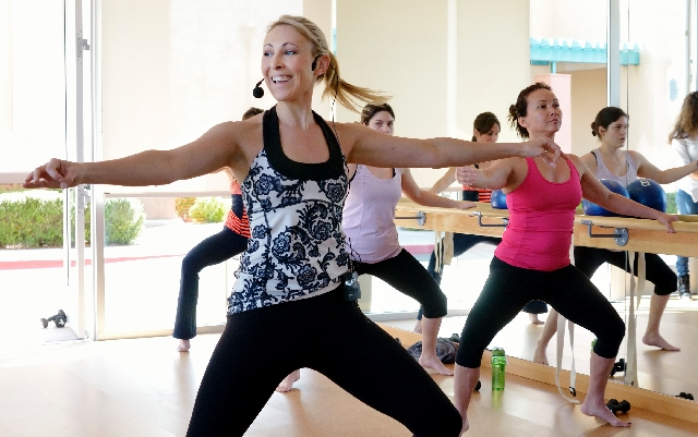 Instructor Meredith Still, left, leads a class at barre3 studio. The studio teaches a fitness practice blending ballet, yoga and Pilates — hence, the 3 — in 60-minute sessions. The &ld ...