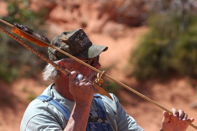 Derek Brockway, of Las Vegas, readies his atlatl throw Friday at the  World Atlatl Contest and Endurance Challenge at Valley of Fire State Park. Below, various atlatls and dart points are on displ ...