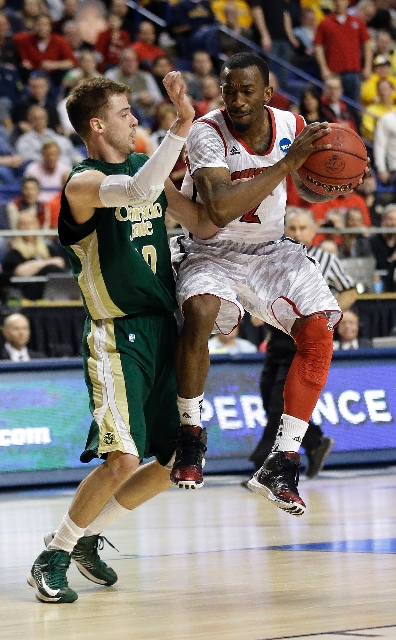 Louisville guard Russ Smith, right, drives against Colorado State guard Wes Eikmeier in the second half Saturday at Lexington, Ky. Smith scored 27 points to lift the top-seeded Cardinals to an 82- ...