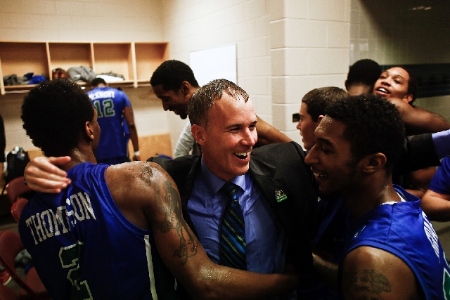Drenched Florida Gulf Coast coach Andy Enfield celebrates with his players, including sophomore guard Bernard Thompson, left, after advancing to the Sweet 16 on Sunday.
