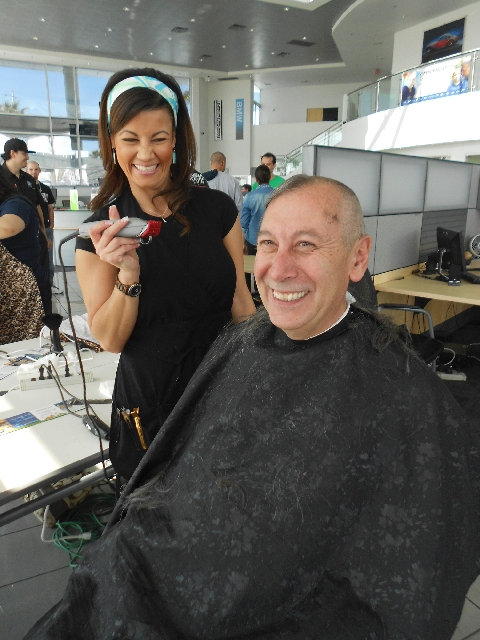 Sunny 106.5 Program Director Tom Chase, a cancer survivor, has his head shaved by Jadee Mangel during the recent benefit for St. Baldrick's at Desert BMW.
