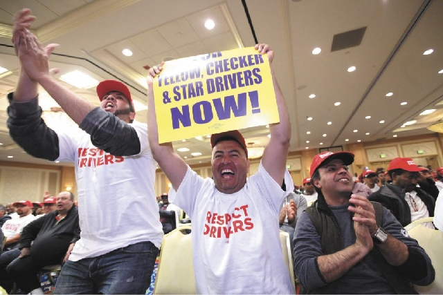From left, taxi drivers Aimad Mouawia, Kamal Lihia and Chakir Benamara cheer during a March 7 membership meeting, at the Gold Coast hotel-casino, of Yellow Checker Star Transportation drivers who  ...