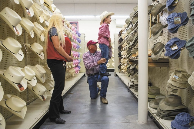 Konnor Wheeler, 6, gets a leg up from his grandfather Keith Wheeler to get a look at his new cowboy hat in a mirror as C-A-L Ranch Stores employee Candice Curtis helps with the selection. The chai ...