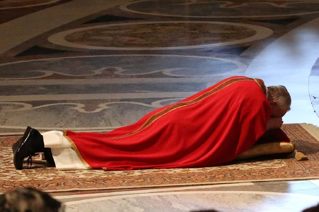 Pope Francis lies down in prayer during the Passion of Christ Mass inside St. Peter's Basilica at the Vatican on Friday. Pope Francis began the Good Friday service at the Vatican with the Pa ...