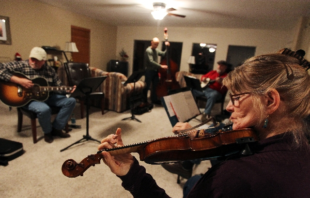 Jeanne Howerton, right, and members of Mountain Crest, a loose-knit group of bluegrass musicians who jam together weekly at Mountain Crest Park, play music together at the home of David Johannesso ...