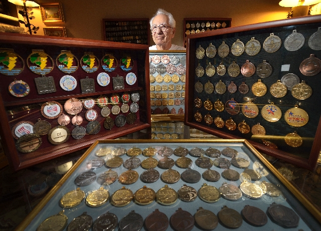 Standing in his Sun City Summerlin home, former swim champion Freddy Leipziger, 85, displays some of the more than 400 medals he has won, March 26. Leipziger started competing in the sport when he ...