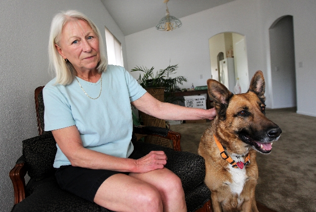 Beth Hultgren, fiancee of Michael Boldon, and their dog, Maxine, pose Thursday in their home in Las Vegas.