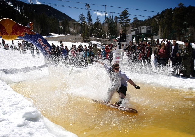 Chris Gutierrez of Las Vegas attempts to cross an icy man-made pond on a snowboard during a pond skim competition Sunday at the Las Vegas Ski & Snowboard Resort, the last day of the ski season. Th ...