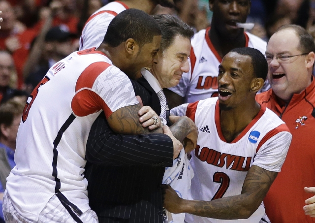 Louisville head coach Rick Pitino celebrates with Chane Behanan, left, and guard Russ Smith (2) after their 85-63 win over Duke in the Midwest Regional final in the NCAA college basketball tournam ...