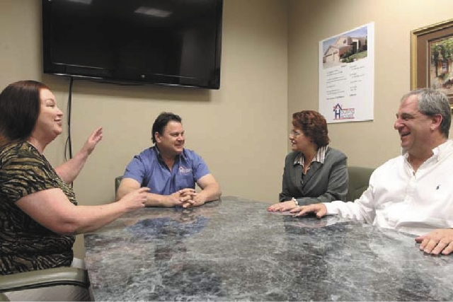 Dave Dziedzic, second from left, is joined by brokers, Jennie Holder, left; Kelly J. Sams, second from right; and David Sajdak in his Housing Angels office March 26. Housing Angels pairs delinquen ...