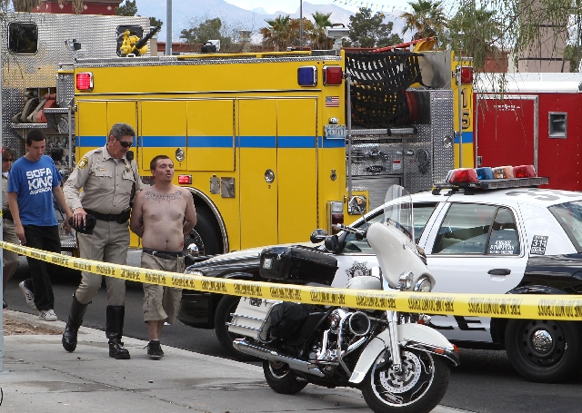 A Las Vegas police officer escorts a man whom witnesses identified as the driver of a car that crashed Monday into the Egg & I on West Sahara Avenue.