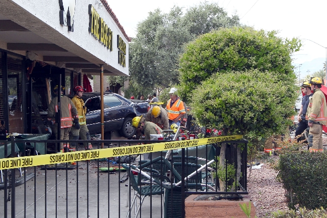 """Las Vegas police and  firefighters work Monday after a car crashed into the Egg & I restaurant, 4533 W. Sahara Ave. Ten people were hospitalized. """"As serious as it was, we are amazed there w ..."""