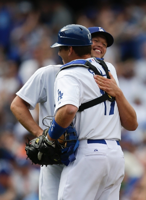 Dodgers catcher A.J. Ellis hugs pitcher Clayton Kershaw after his 4-0 shutout win over the Giants.
