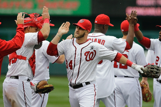 Nationals left fielder Bryce Harper (34) congratulates teammates after a 2-0 win over the Miami Marlins on Opening Day on Monday at Washington. Harper homered twice.