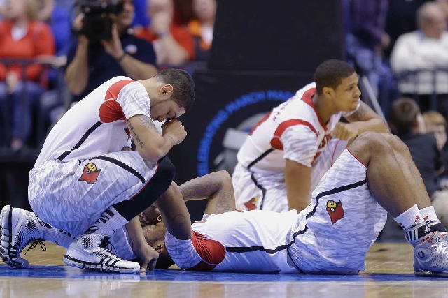 Louisville's Peyton Siva, left, Chane Behanan, center, and Wayne Blackshear (20) react to Kevin Ware's injury during the first half of the Midwest Regional final in the NCAA college ba ...