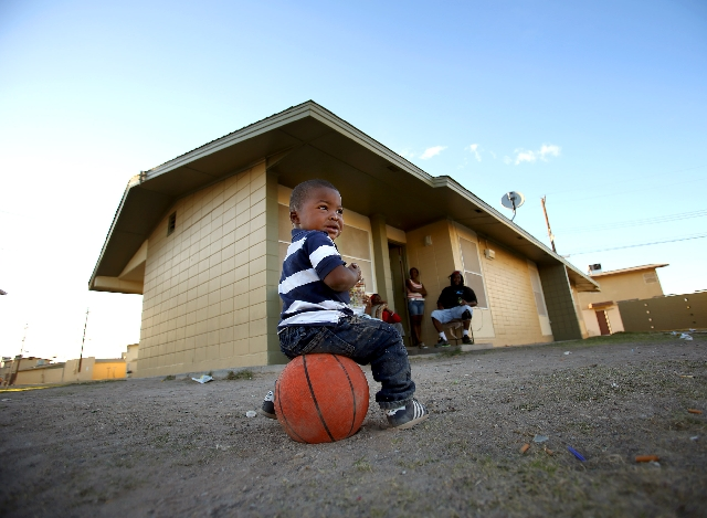 Marshawn Alexis, nearly 2 years old, sits Tuesday at Sherman Gardens Annex while his family gathers behind him. A shooting earlier in the week about a block from the Alexis family home left six pe ...
