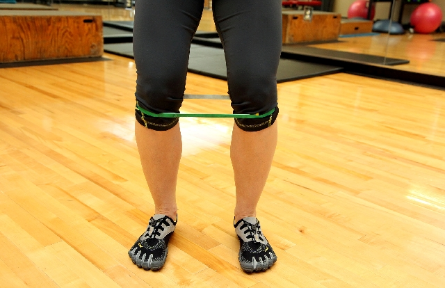 Tube walking, START: Position a resistance band around the legs below the knees. Stand with the feet at hip width. Hinge at the hip and allow the knees to bend while keeping the core tight and bac ...