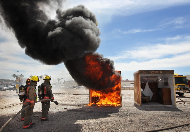 Firefighters from Clark County and North Las Vegas wait to extinguish a controlled blaze during a demonstration of sprinkler use at the Clark County Fire Department Training Center on Wednesday.