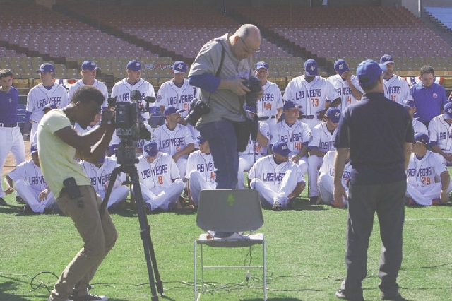 Team photographer Steve Spatafore, middle, checks his exposure while taking the official Las Vegas 51s team portrait during media day at Cashman Field in Las Vegas on Tuesday. The 51s open their 3 ...