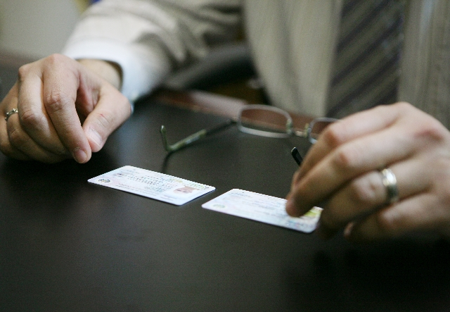 Two official El Salvador identification cards are shown in front of Tirso Sermeno, general counsel of the El Salvador Consulate in Las Vegas.