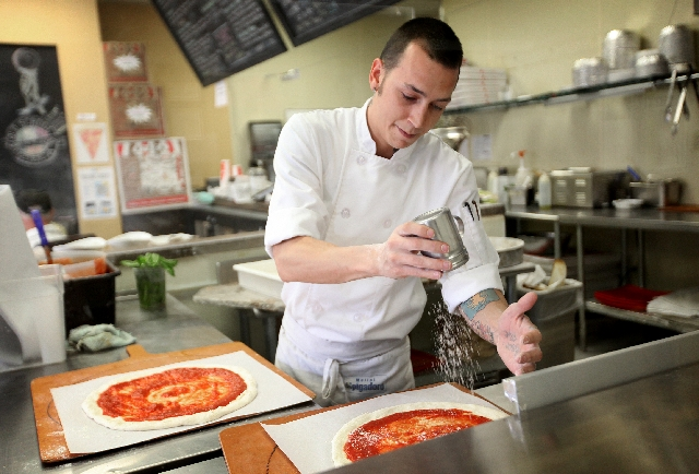 Anthony Rothenberg makes pizzas at Old School Pizzeria on Craig Road. Pizzeria owner Giovanni Mauro is a purist. His sauce is flavored largely by tomatoes and he uses natural yeast in his dough.