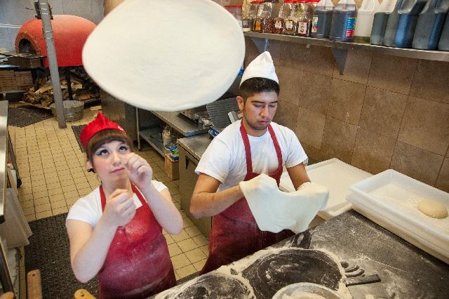 "Pizza-makers Amber Isen, left, and Louis Chavarria toss pizza dough at Novecento. When baked, the dough undergoes the ""leopard effect,"" forming charred spots while in the wood-burning  ..."