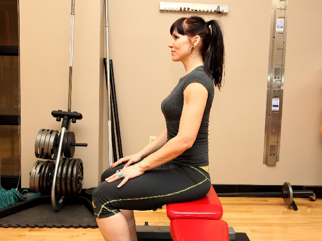 SQUAT WHILE SITTING, START: Position the feet outside shoulder width. Contract the core and straighten the back.