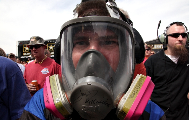 Joe Shover, a government contractor from Washington, D.C., wears a gas mask while standing near Antron Brown's Top Fuel dragster on Saturday at the SummitRacing.com NHRA Nationals at The Str ...