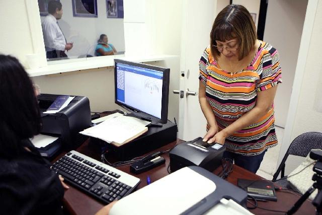 Angela Lopez de Mejorado, 53, right, has her fingerprints scanned by Maria Elena Rivera while applying for an official El Salvador identification card at the El Salvador Consulate. De Mejorado is  ...