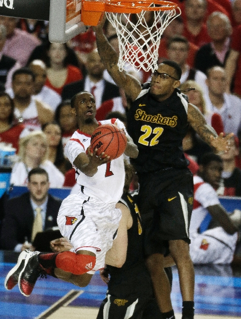 Louisville guard Russ Smith drives on Wichita State's Carl Hall during the second half of the teams' national semifinal Saturday at Atlanta. Smith scored a team-high 21 points for the  ...