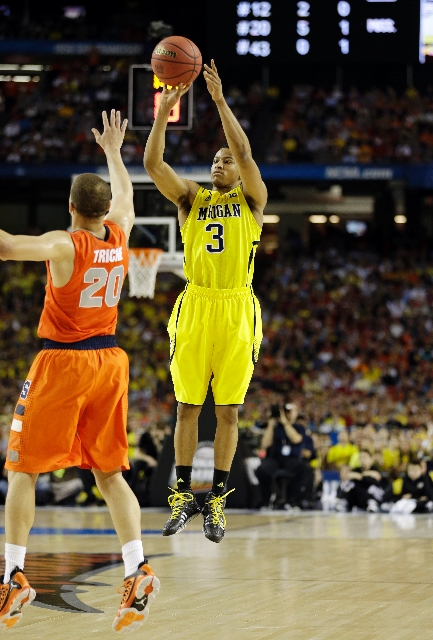 Michigan guard Trey Burke shoots over Syracuse's Brandon Triche during the teams' national semifinal Saturday at Atlanta. Burke was held to one basket, but the Wolverines advanced, 61-56.