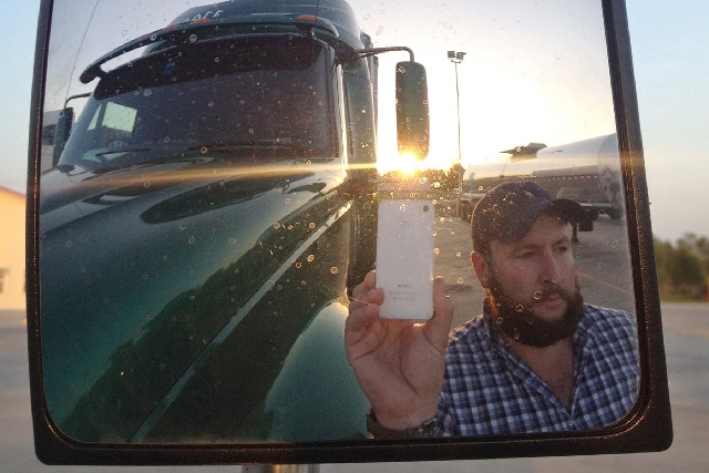 This image provided by James Weitze shows a truck driver taking a self-portrait on the road. Weitze satisfies his video fix with an iPhone. He sleeps most of the time in his truck, and has no apar ...