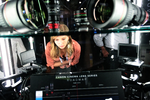 A conventioneer looks at lenses Monday at Canon's booth at the National Association of Broadcasters' expo. Show officials hope to top last year's attendance of 91,000.