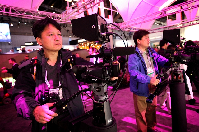 Kye-Young Choi of South Korea, left, checks out a video camera at the JVC booth at the National Association of Broadcasters' NAB Show on Monday at the Las Vegas Convention Center. The show i ...