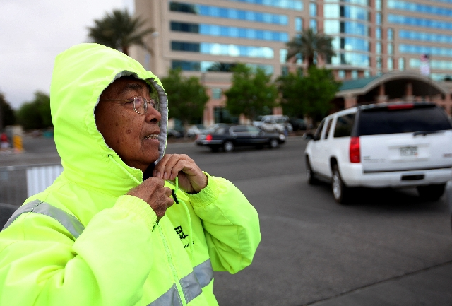 Jun Obinque secures a jacket hood while performing traffic attendant duties in high winds Monday at the Las Vegas Convention Center. A wind advisory has been issued again for today for the Las Veg ...