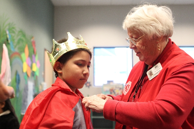 Foster grandparent Mary McConnelly helps put a cape on 9-year-old Jesus Velazquez during an acting class at the Cambridge Recreation Center.