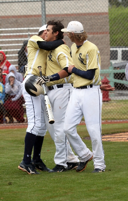 Shadow Ridge's Ben Fitzhugh is congratulated by teammates Cory Royer, left, and Travis Caskie after hitting a home run Monday.