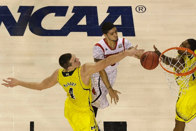 Louisville guard Peyton Siva (3) shoots against Michigan forward Mitch McGary (4) and Michigan forward Glenn Robinson III (1) during the first half of the NCAA Final Four tournament college basket ...
