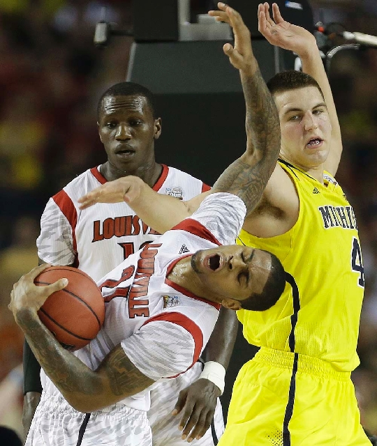 Louisville forward Chane Behanan (21) grabs the ball as Michigan forward Mitch McGary (4) looks on during the first half of the NCAA Final Four tournament college basketball championship game Mond ...