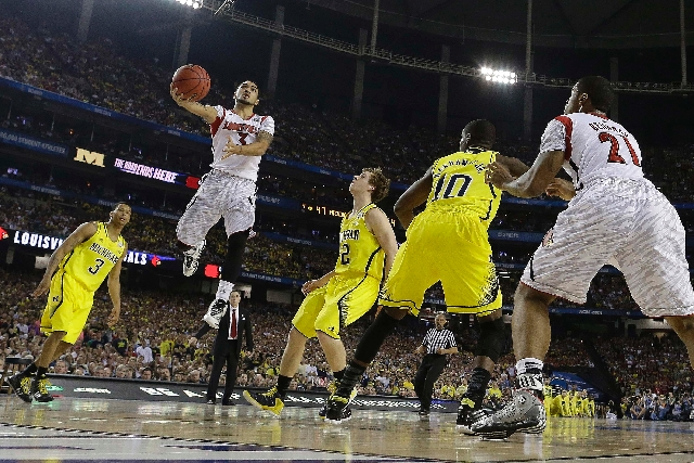 Louisville guard Peyton Siva (3) heads to the hoop against Michigan during the second half of the NCAA Final Four tournament college basketball championship game Monday in Atlanta.