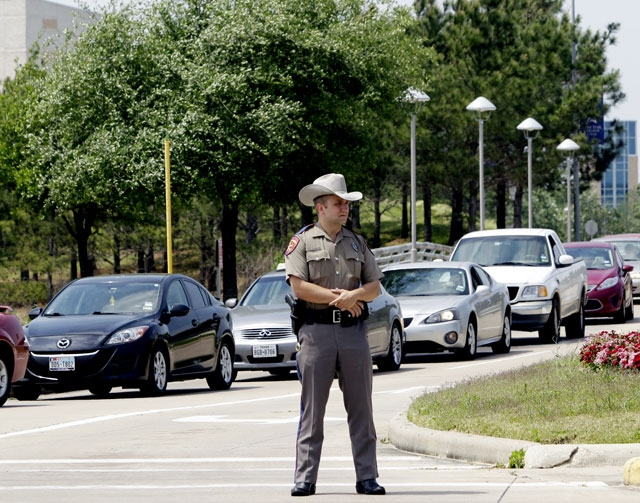 A Texas State Trooper stands at an entrance as vehicles leave from the Cy-Fair campus of Lone Star Community College in Cypress, Texas on Tuesday. More than a dozen people were wounded when a susp ...