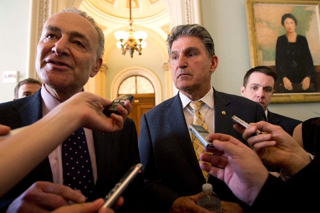 Sens. Chuck Schumer, D-N.Y., left, and Joe Manchin, D-W.Va. speak to reporters as they walk from U.S. Sen. Majority Leader Harry Reid's, D-Nev., office on Capitol Hill in Washington on Tuesd ...