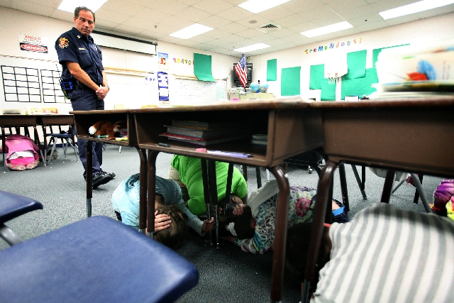 Capt. Scott Straily, a Clark County firefighter, observes to ensure students are performing an earthquake safety drill correctly at Beatty Elementary School in Las Vegas on Tuesday. It was the fir ...