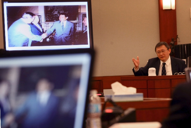 Hong Kong businessman Richard Suen testifies Tuesday at the Clark County Regional Justice Center in Las Vegas. The photo on the monitor shows Bill Weidner, left, former president and chief operati ...