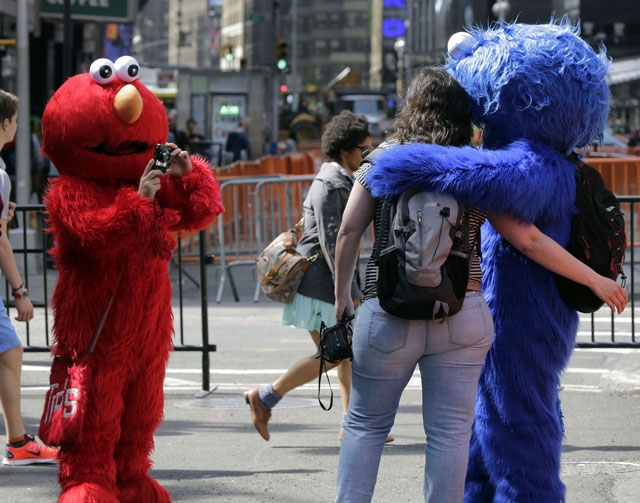 An Elmo character, left, uses a woman's camera to photographer her with a Cookie Monster character, in New York's Times Square on Tuesday.  A string of arrests in the last few months h ...