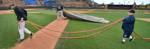 Larimer and Cutler carry a hose off the field after watering the base paths.