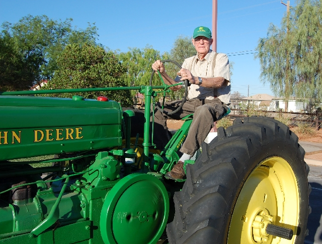 Henderson author Ken Hinman sits in the seat of Jimmy John, the John Deere tractor that inspired his new children's book.